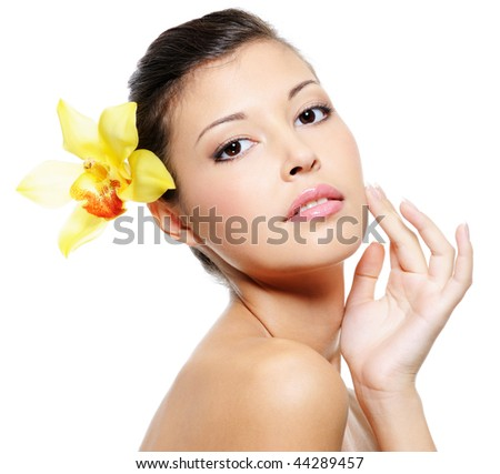Beauty asian woman with a wellness skin of her face with a yellow orchid from her ear - stock photo