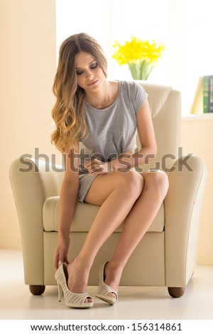 Beauty at home. Beautiful young woman in dress wearing shoes - stock photo