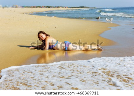 Beauty at the beach with blue sky and sand around Beautiful young woman writing the sand