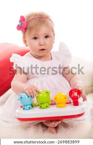 Beauty baby girl eight months age playing with colorful toys with animals - stock photo
