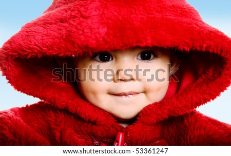 Beauty baby looking at the camera with red hood over sky background