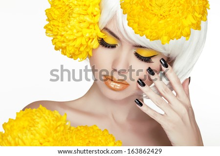 Beauty Blond Female Portrait with yellow flowers. Beautiful Spa Woman Touching her Face. Makeup and manicured nails. Perfect Fresh Skin. Isolated on white background - stock photo