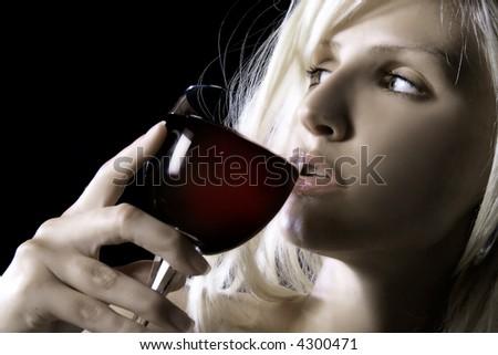 beauty blond girl is drinking wine - stock photo