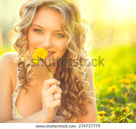 Beauty blond model girl lying on a field and smelling dandelion flowers. Allergy free. Beautiful Young Woman in the Meadow.  Outdoors. Enjoy Nature. Healthy Smiling Girl portrait - stock photo