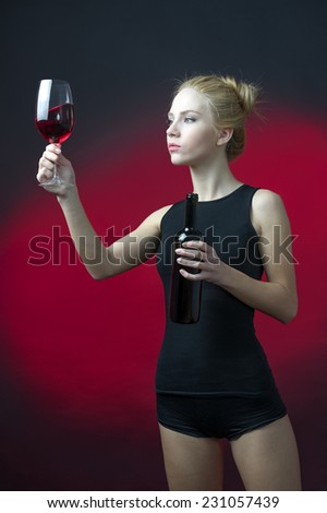 beauty blond model holding wineglass with red wine and black bottle looking the red color of wine  - stock photo