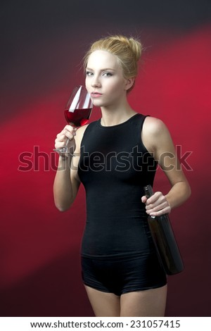 beauty blond model holding wineglass with red wine and wine bottle getting ready to take a sip  - stock photo