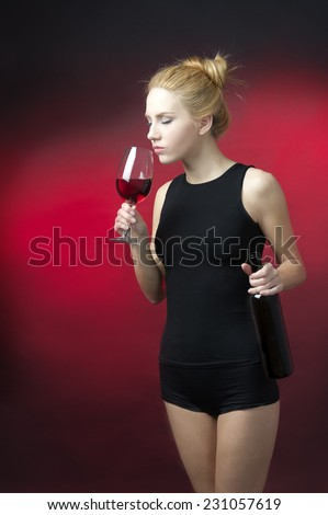 beauty blond model holding wineglass with red wine and wine bottle snif wine - stock photo