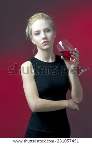 beauty blond model holding wineglass with red wine looking into camera  - stock photo