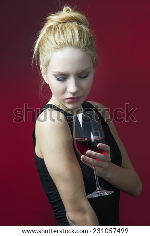 beauty blond model holding wineglass with red wine looking into glass  - stock photo