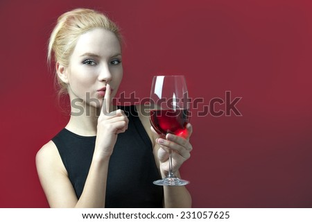 beauty blond model holding wineglass with red wine making gesture of silince  - stock photo