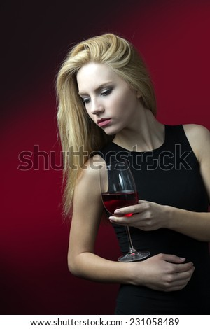 beauty blond model holding winglass with red wine  - stock photo