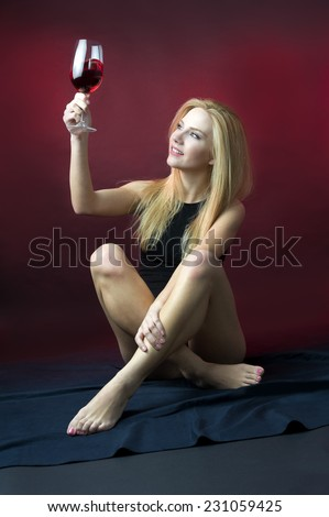 beauty blond model sitting down holding wine glass checking the color of red wine looking into glass  - stock photo