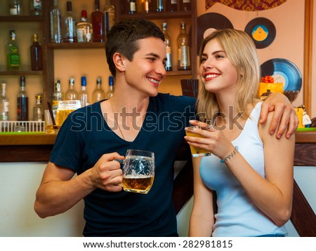 Beauty blonde woman and brunette man smiling and drinking in bar. horizontal photo - stock photo