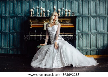 Beauty Blonde Woman Portrait. Beautiful bride with long curly blond hair sitting at the piano. Full length portrait. White Hair. Sexy model. Perfect Skin and Make up. Hair Extensions. Looking away - stock photo