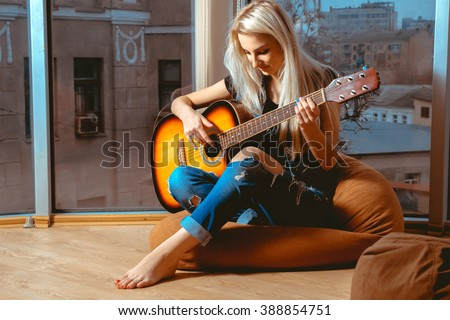 Beauty blonde woman trying to play guitar. Girl with guitar. Woman playing guitar. leisure with guitar. - stock photo