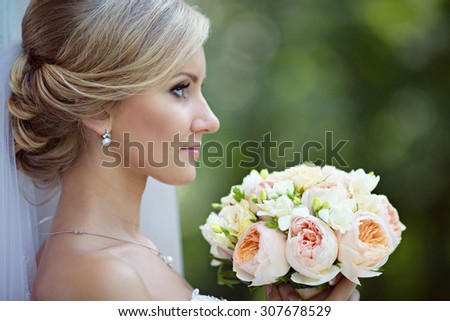 Beauty bride in bridal gown with bouquet and lace veil on the nature. Beautiful model girl in a white wedding dress. Female portrait in the park. Woman with hairstyle. Cute lady outdoors - stock photo