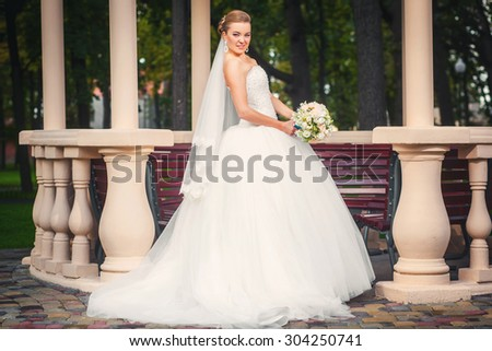 Beauty bride looking in camera and posing in modern park