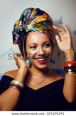 beauty bright african woman with creative make up, shawl on head like cubian closeup smiling - stock photo