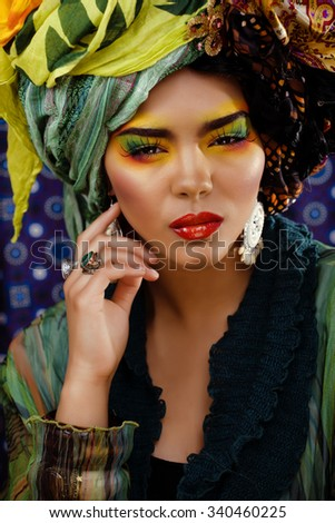beauty bright woman with creative make up, many shawls on head like cubian woman, ethno look closeup