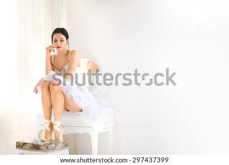 Beauty brunette ballerina in stylish room, wearing white ballet skirt and corset - stock photo