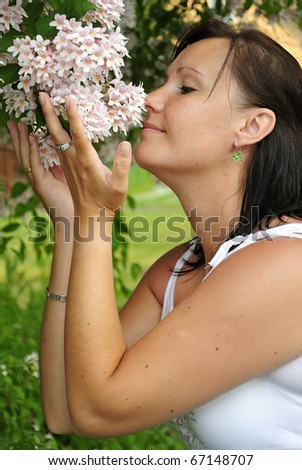 Beauty brunette sniffing summer flowers
