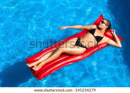 Beauty brunette sunbathing in the pool, lying on a red mat - stock photo