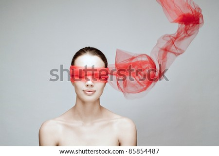 Beauty brunette with red ribbon on eyes - stock photo