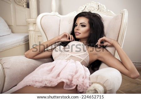 Beauty brunette woman in stylish room, wearing pink costume, ballet skirt and corset - stock photo