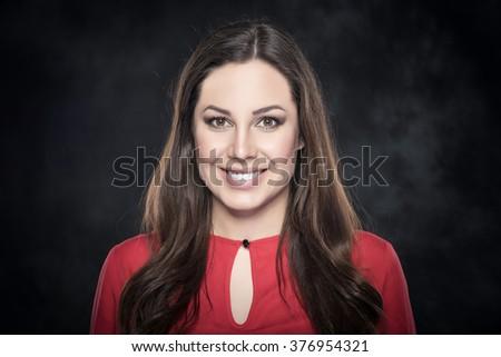 Beauty brunette woman smiling on dark background. - stock photo
