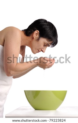 beauty care: mature woman washing her face. isolated on white background - stock photo