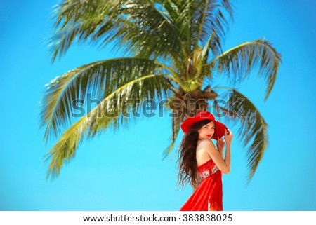 Beauty Carefree young girl with red hat relaxing on tropical beach with exotic Palm tree. Summer outdoor portrait. Lifestyle. Bliss freedom concept.  - stock photo