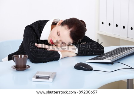 Beauty caucasian businesswoman sleeping on the desk in the office.