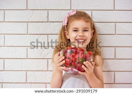 beauty child enjoying a fresh strawberry - stock photo