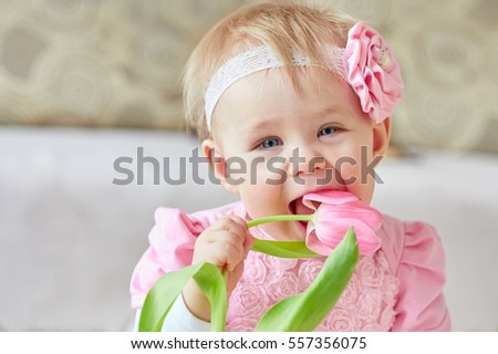 Beauty child girl in a pink dress tastes tulip flower