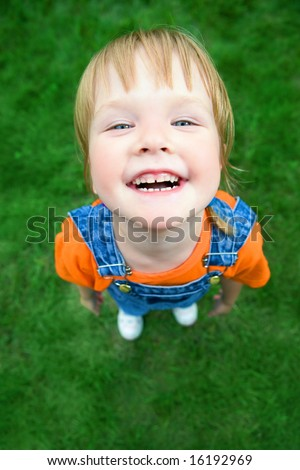 beauty child portrait from above  perspective on green grass - stock photo