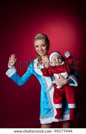 Beauty christmas girl play with baby santa claus - stock photo