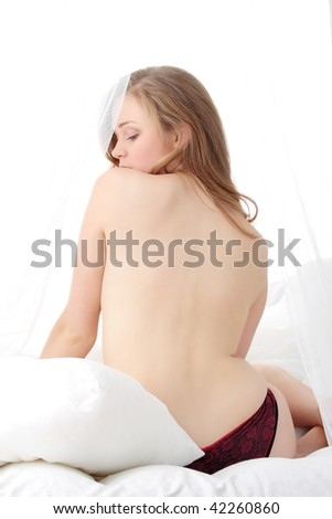 Beauty close-up of young sensual naked woman lying on the bed - stock photo