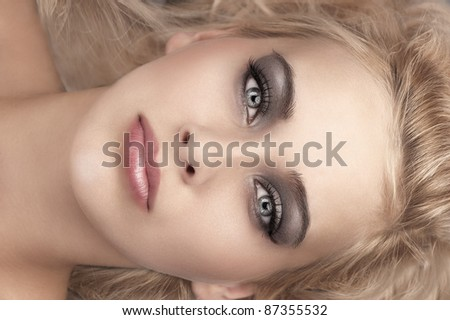 beauty close up portrait of a laying blonde with grey eyes, smokey eyes make up and soft pink glossy lips - stock photo