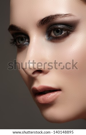 Beauty close-up portrait of beautiful sexy woman model with dark evening catwalk fashion eyes make-up and pale lips on gray background - stock photo