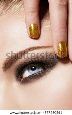 Beauty close up. Smokey eye makeup and gold manicured nails. Party make-up. - stock photo