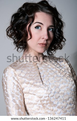 Beauty closeup portrait of a beautiful young brunette woman model with curly hair, tender makeup wearing light golden color dress, looking up aside, dreaming of something. Gray background