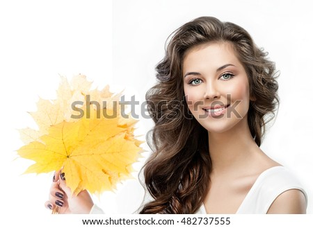 beauty closeup portrait of attractive caucasian smiling woman brunette isolated on white studio shot lips toothy smile face hair looking at camera tooth hand holding yellow marple autumn leaves