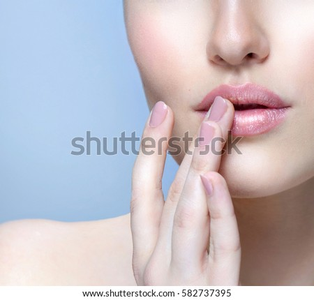 beauty closeup portrait of attractive young  caucasian woman brunette on blue background studio shot lips care face skin care applying cream head and shoulders looking up hands