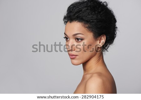 Beauty closeup profile portrait of beautiful mixed race caucasian - african american woman looking out of frame, isolated on gray background - stock photo
