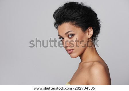 Beauty closeup profile portrait of beautiful mixed race caucasian - african american woman looking at camera, isolated on gray background - stock photo