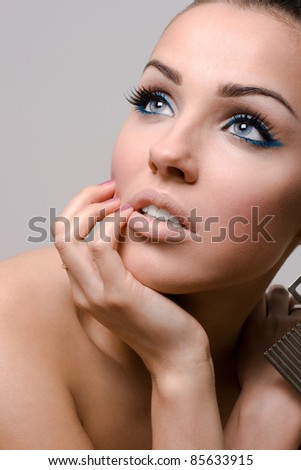 Beauty closeups of an attractive brunette posing on grey background - stock photo