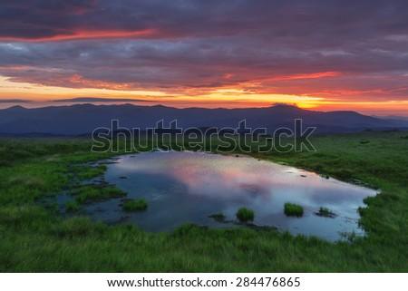 Beauty colorful sanset in the Carpathian mountains with small lake. Marmarosu ridge, Ukraine, Europe.  - stock photo