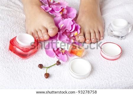beauty composition - feet with acrylic toenails, flowers and crystals - stock photo