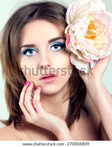 beauty concept - clean face of beautiful young woman with big blue eyes, touching her face, flower in hair - stock photo