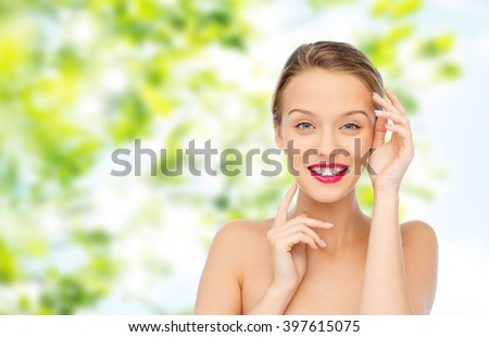 beauty, cosmetics, people and health concept - smiling young woman with pink lipstick on lips touching her face over green natural background - stock photo